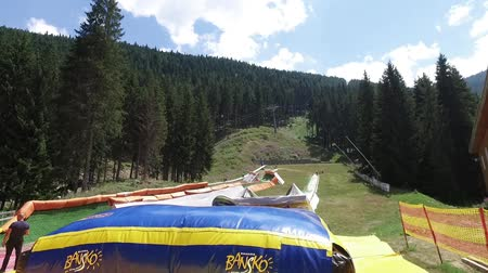 stimulating : New adrenaline attraction, summer tubing with high jump. Children enjoy sliding down at high speed and jumping down the inflatable rubber bed Stock Footage