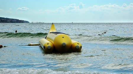 stimulating : Colorful Banana boat anchored in shallow water move on sea waves Stock Footage