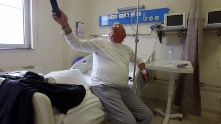 positive ageing : Senior man in a hospital bed with drip in his hand changing TV chanels. Recovery after operation
