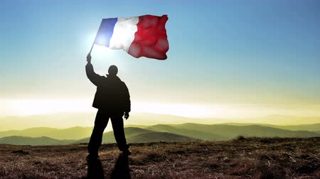 conquest : Successful silhouette man winner waving French flag on top of the mountain peak. Cinemagraph LOOP background