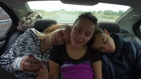 carseat : Three sleepy happy teens driving at car back seat