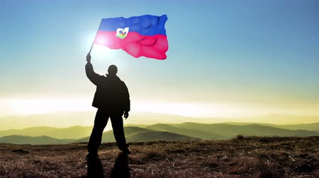 conquest : Successful silhouette man winner waving Haiti flag on top of the mountain peak. Cinemagraph LOOP background