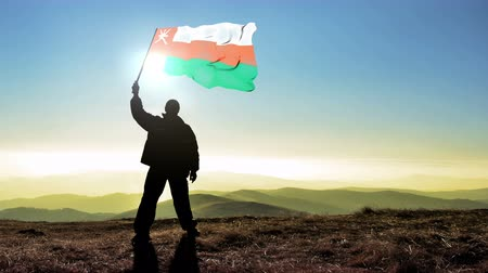 conquest : Successful silhouette man winner waving Oman flag on top of the mountain peak, Cinemagraph LOOP background