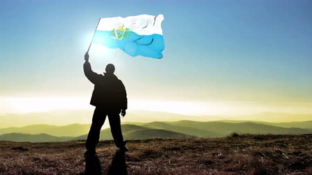conquest : Successful silhouette man winner waving San Marino flag on top of the mountain peak, Cinemagraph LOOP background