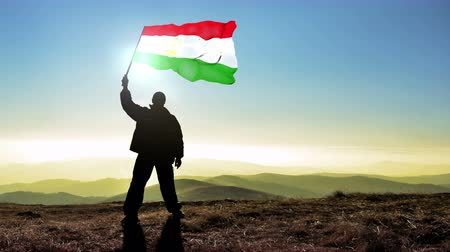conquest : Successful silhouette man winner waving Tajikistan flag on top of the mountain peak, Cinemagraph LOOP background