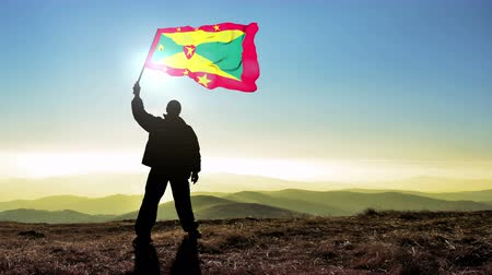 conquest : Successful silhouette man winner waving Grenada flag on top of the mountain peak. Cinemagraph LOOP background
