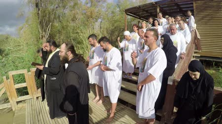 baptized : People are waiting to be baptized by water during a baptism ritual at Qasr el Yahud near Yericho on the Jordan river Stock Footage