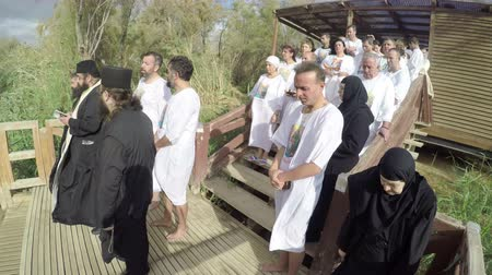 baptized : Religious christians with white clothes going into the water of the Jordan river at baptismal site Qasr el Yahud near Yericho