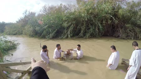 baptized : Christian pilgrims during mass baptism ceremony at the Jordan River in North Israel.In Christian tradition  Jesus was baptised in the River Jordan by John the Baptist