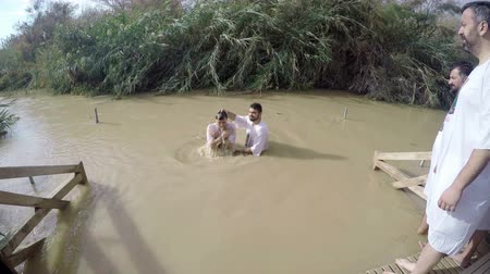 baptized : a man gets baptised in the Jordan River  during a mass celebration. The man's head splashes into the water as he dives
