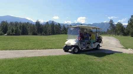 boggy : group of friends driving golf cart in country club during summer holiday Stock Footage
