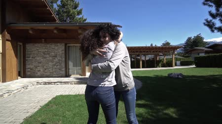 toka : Mother  daughter love. Two woman exchange hugs and kisses at meeting in front of luxury house  SLOW MOTION