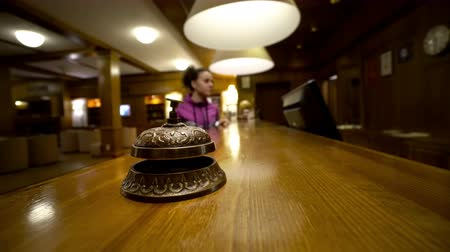 sinos : Nervous girl ringing hotel reception bell  hand pushing accommodation call bell on wooden reception front desk