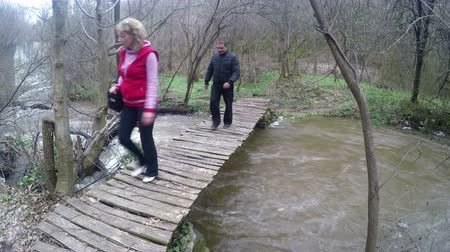 voluntário : Three hikers walk over old wooden bridge river flooded from heavy rains