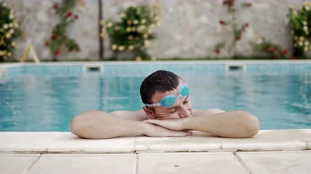 amontoado : Handsome man with googles enjoy luxury swimming pool side  cinematic dof