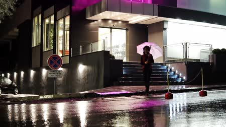 andar : Beautiful brunette girl with umbrella walking at rainy night