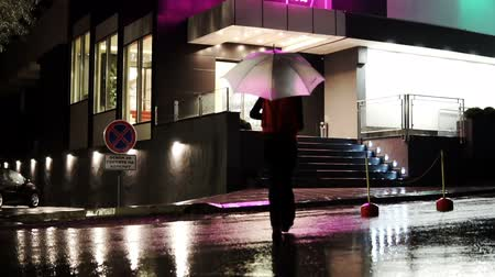 coming home : Woman walking away under colorful umbrella towaard entrance door in the evening