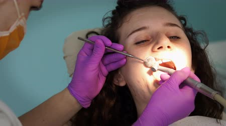 surgical tools : Female dentists working with turbine on young girl patient.Dentist's office