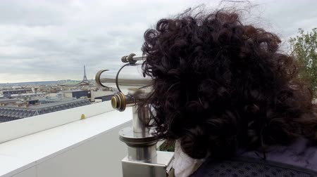 lookout point : Tourist woman enjoy Paris cityscape view with coin binocular telescope at top terace balcony in Galery Lafayette