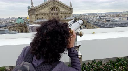 lafayette : Tourists looking over Paris cityscape with Opera Garnier and Eiffel Tower on Lafayette Gallery terrace with coin operated binocular telescope