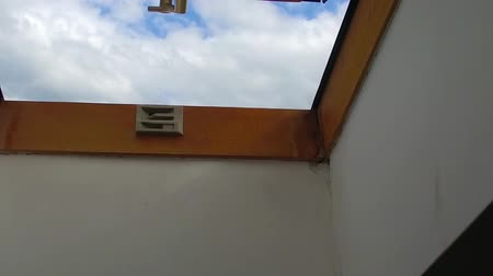 sem nuvens : Open window on the roof with blue sky. Skylight in the attic Vídeos