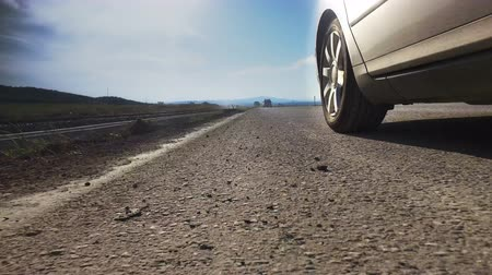 tread : Driving a sport car on a country road. Back wheel spinning POV