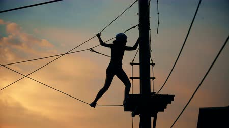 védősisak : pretty girl silhouette in helmet and protective equipment in extreme sports competitions adrenaline park at sunset