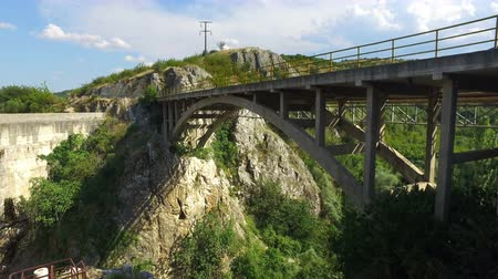 liken : Bridge and road of the rural road over canyon. A car is seen driving on the bridge