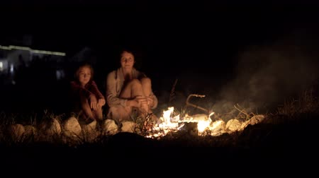 Mother and daughter sit at night round a bright bonfire Stock Footage