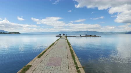 Moving on fishermans port on Ohrid lake with calm water reflection and blue sky