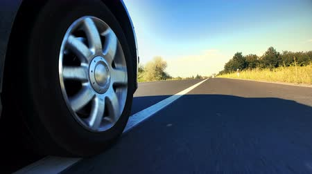 Fast speed car wheel spinningon rural road asphalt, Point of View Stock Footage