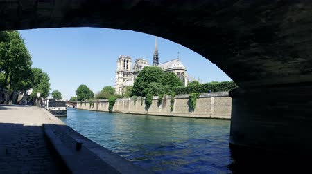 Sunny day notre dame de paris. Pov cinematic moving from under the bridge