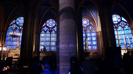 Interior of the Gothic Church of Notre Dame de Paris stained glass windows during a church ceremony.