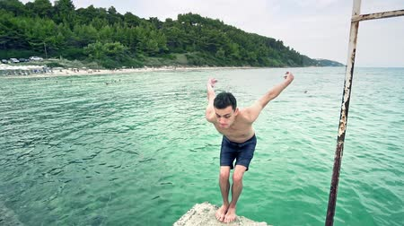 レクリエーション : Sport jumping boy makes back flip in sea turquoise water, SLOW MOTION 動画素材