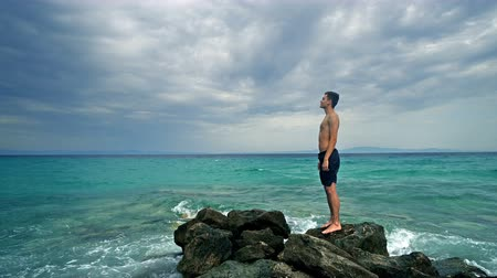 navigator : Lost alone male teen standing on sea rock and navigating horizon