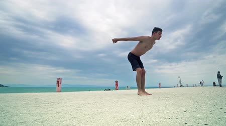 backflip : Full body portrait of parkour man jumping high on the beach performing a back flip, SLOW MOTION