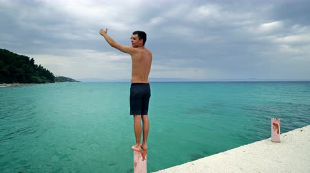 leegte : Young men having speech standing on post at pier on empty beach with turquoise water