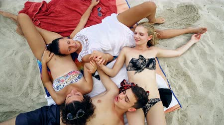 pozisyon : group of friends lying on the beach in a sunny day. concept about mixed race friends and vacations Stok Video