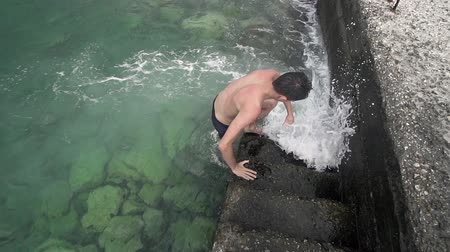 Handsome sport fit boy come out of sea water on port stairs, SLOW MOTION