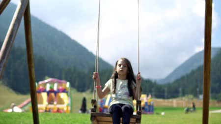 Slow Motion Sequence Of Girl On Swing In Playground , cinematic dof