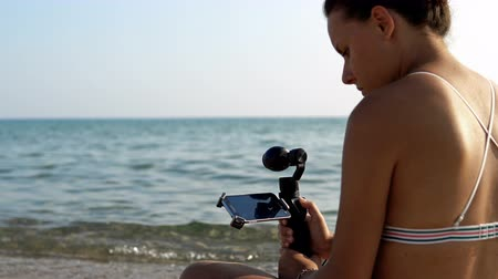 stabilizátor : Attractive female records video with modern 3d gimbal stabilized camera and smartphone