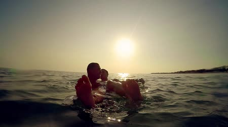 отцовство : Two friends, father and son exchange emotions playing in sea at sunset, slow motion