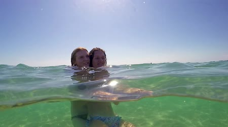 origin : Beauty portrait of two teenager girls of different ethnic origins hugging and kissing, smiling by a spacious turquoise sea on a summer holiday, outdoors. Travel lifestyle, nature beach exterior, camera dome half underwater view, SLOW MOTION