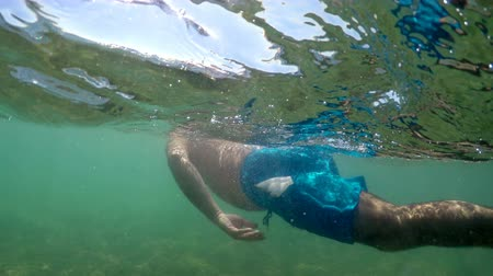 masque de plongée : Following a man with mask snorkeling, swimming on sea water surface, camera dome half underwater view