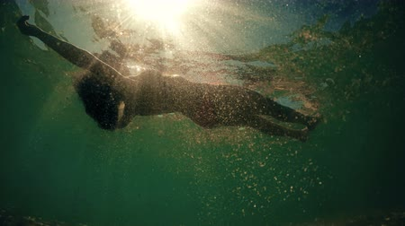 fundo : Woman floating on water at sunset, bottom of the sea POV