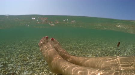 купол : Female feet relaxing floating in sea shallow water, summer vacation concept, half underwater view camera dome shot