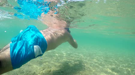 mergulhador : Man with snorkeling mask swimming on sea water surface searching for treasure, camera half underwater view