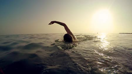 plavat : Professional sport man swim crawl in sea at sunset, cinematic slow motion trekking shot