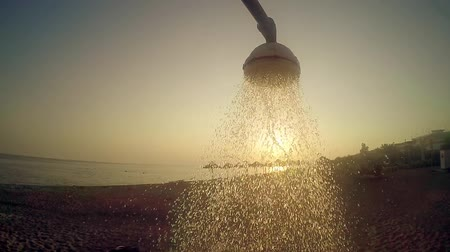 faucet : Beach head shower with running water against sunset sun, summer concept, SLOW MOTION