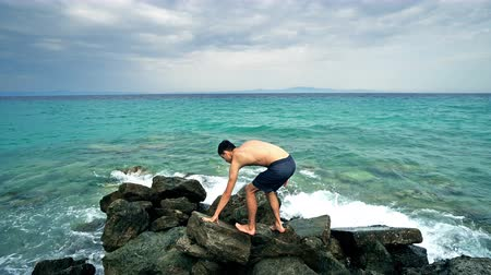 výrazy : Lost alone male teen standing on sea rock and navigating horizon